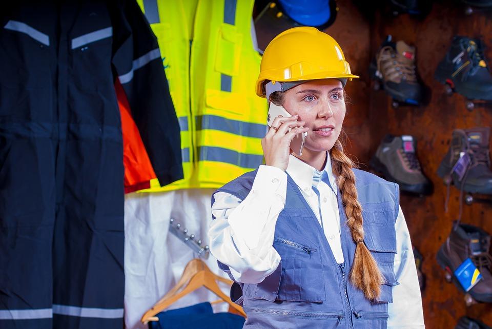 odszkodowanie za wypadek w pracy- dzielwczyna w kasku i stroju roboczym dzwoni telefonem