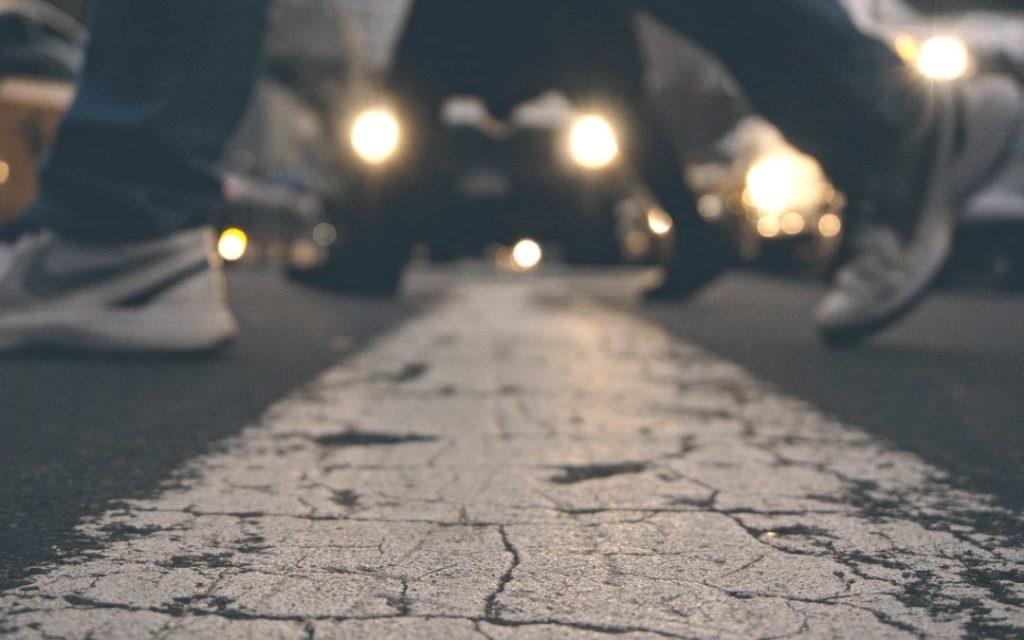 ciemy dzień, przechodzące po pasach nogi pieszych