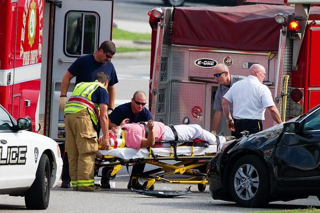 renta- poważnie chory człowiek transportowany na noszach w tle samochody