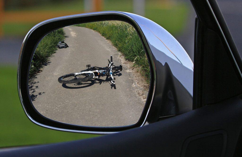 rower w lusterku wstecznym lezący na asfalcie