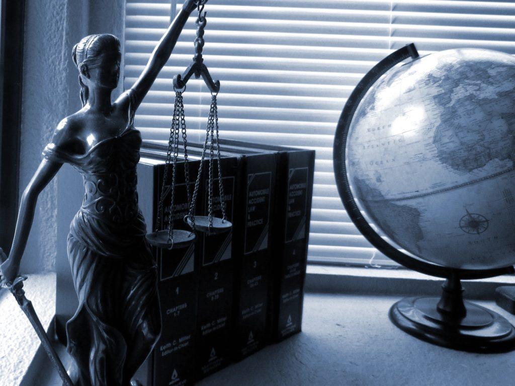 koszt sprawy cywilnej o odszkodowanie- Temida, globus i książki prawnicze na biurku