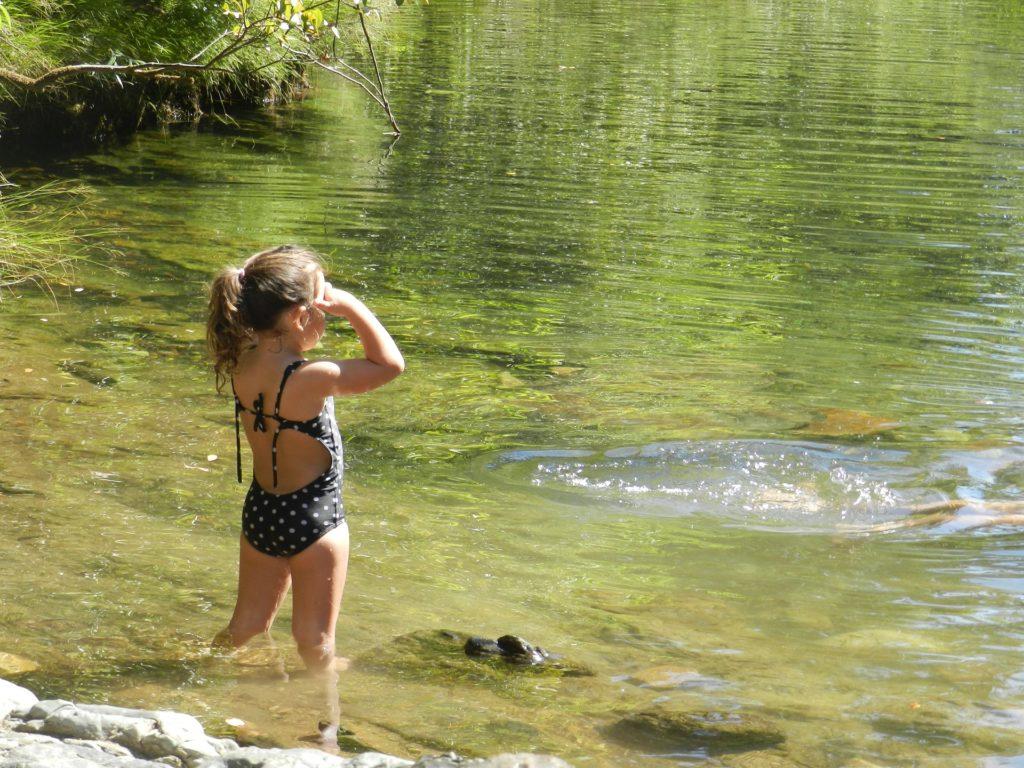 wypoczynek nad wodą- dziewczynka wchodzi do wody